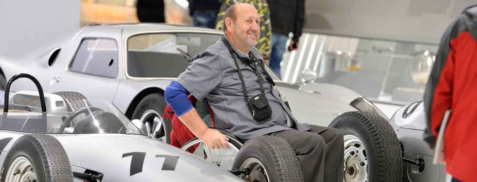 Ein Mann im Rollstuhl fährt zwischen den Rennwagen aus den 1950ern durch die Ausstellung.