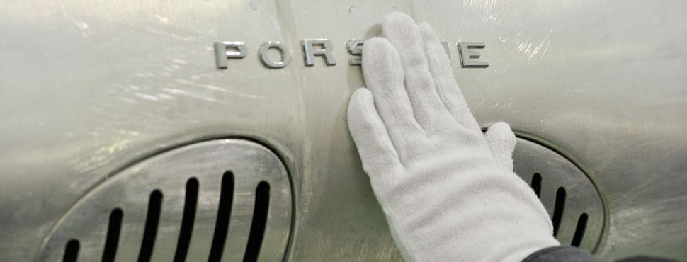 Ein Besucher ertastet mit einem Handschuh den Porsche Schriftzug an einem Fahrzeug.